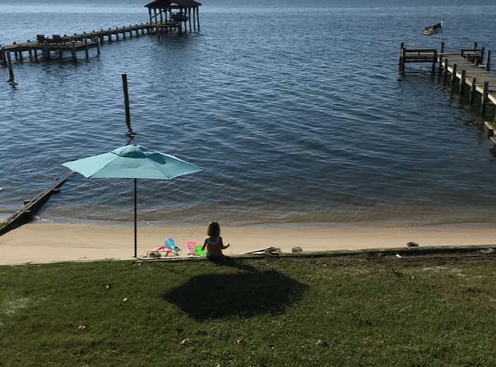 Little Girl Under an Umbrella by the Beach
